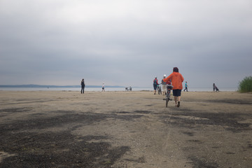 people walk by the sea on a cloudy day