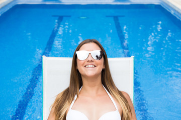 Smiling pretty woman in sunglasses resting in deck chair at poolside.