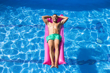 Handsome man smiling and tanning on airbed in pool with eyes closed.