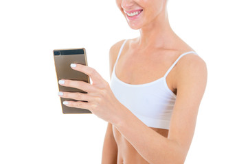 Gorgeous slim woman wearing Sportswear with perfect female body takes a selfie with her smart-phone, isolated on white. Close-up studio photography.