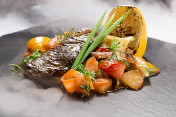 fish with vegetables in sauce on slate table