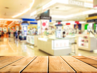 Abstract blur and defocused beautiful luxury shopping mall department and retail store interior for background and empty wooden table space platform for present product.