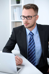 Portrait of businessman sitting at the desk in office workplace