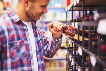 Young man choosing and buying wine in supermarket