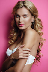 Beautiful happy blonde young woman posing in white lingerie. Ideal slim sexy body. Girl with long curly hair. pink  background. Glamour makeup.