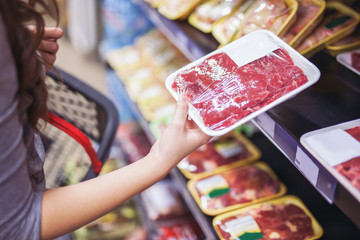 Close up of woman holding wrapped meat in grocery store