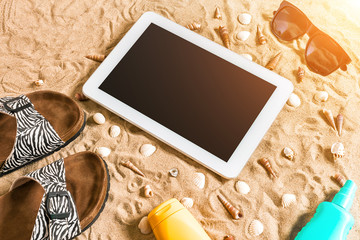 Summer flip-flops, tablet, sunglass and seashell on sand. With place for your text. Top view