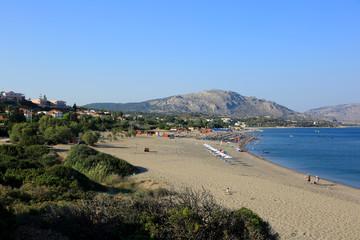 Piękna plaża na Rodos w Grecji, parasole i leżaki na plaży wzdłuż morza.