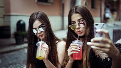 Two cute girls are drinking cold fruit drinks while sitting in a restaurant on the street on a sunny day and taking the selfie for instagram. Conception: social networks and girls.