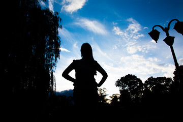 Silhouette of a girl against a blue sky playing with her hair
