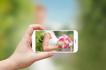 Taking photo of bride with wedding bouquet in hands with smartphone