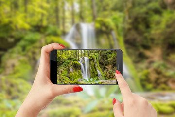 Taking picture of waterfall with smartphone in the forest