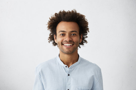 Positive guy with African hairstyle and dark skin wearing elegant white shirt looking cheerfully into camera isolated over white background. Young dark-skinned male with smile dressed elegantly