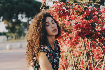 Hipster girl with long dark hair is looking at the red flowers while standing amidst the bushes at the city park. Female student wearing colorful dress is having rest at the garden on a break time.