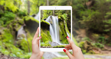 Taking picture of waterfall with tablet