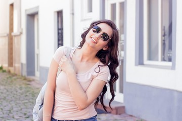 Young beautiful woman brunette walks at the city in Europe. Summer. Happy girl. Street fashion.