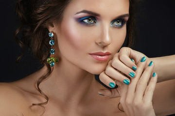 Woman with a beautiful makeup and hairstyle wearing shiny earrings