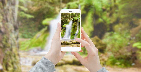 Woman with smartphone in the woods taking photo of waterfall
