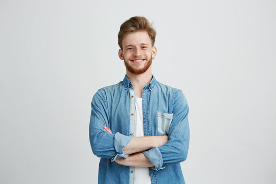 Portrait of young handsome man in jean shirt smiling looking at camera with crossed arms over white background.