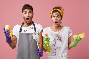 Handsome male wearing apron standing near his wife holding cleaning equipment having shocked look. Couple looking at dirty room with bugged eyes and jaw dropped not wanting to clean it again Wall mural