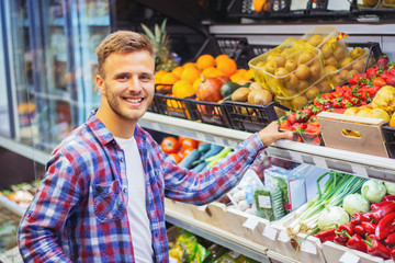 Young man buying fruit in grocery store.
