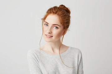 Portrait of beautiful tender redhead girl smiling posing looking at camera over white background.