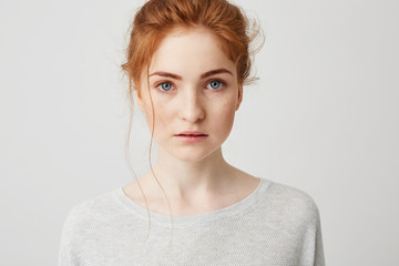 Portrait of beautiful tender ginger girl with blue eyes posing looking at camera over white background.