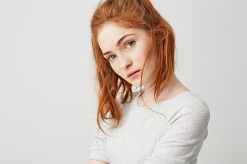 Close up of young tender girl with beautiful red foxy hair looking at camera over white background. Copy space.