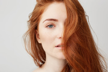 Close up of young tender beautiful girl with red hair looking at camera over white background.