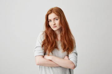 Portrait of beautiful ginger girl with freckles looking at camera with crossed arms over white background.