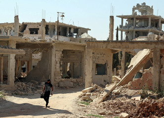 A Free Syrian Army fighter carries a weapon as he walks past damaged buildings in a rebel-held part of the southern city of Deraa
