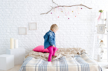 Happy child girl jumps on bed