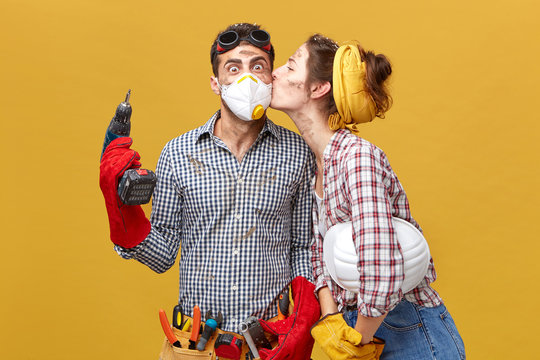 Pretty female kising her husband in cheek being thankful to him for repearing her wardrobe. Surprised male worker in mask holding drilling machine being glad to recieve kiss from his girlfriend