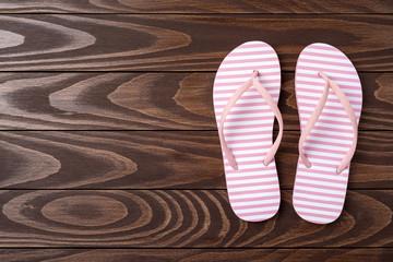 Overhead shot of pink flip flops on wooden background