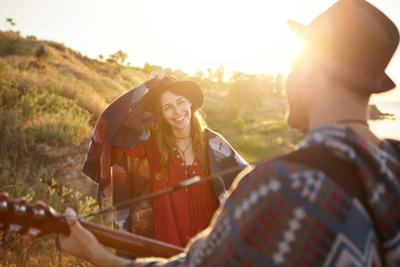 Cheerful woman in black hat and red blouse having scarf on shoulders looking with sympathy at her husband who is playing guitar to her standing at greenland. Young musician singing songs outdoors