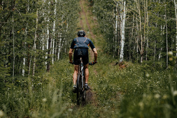 back mud man athlete mountain bike in forest