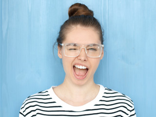 Close up portrait of a happy young hipster european teen girl in nerdy square glasses blinking at camera in a playful manner, smiling and winking, shouting loudly, standing against blue background
