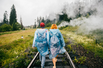 Couple of lovers smoking electronic cigarette on railroad outdoor at nature in raincoats in cloudy smuggy day. Rebel travelers on vacation. Danger zone. Rest at weekend. Bad habbit. Pulmonary disease