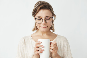 Beautiful tender girl in glasses holding cup looking down over white background.