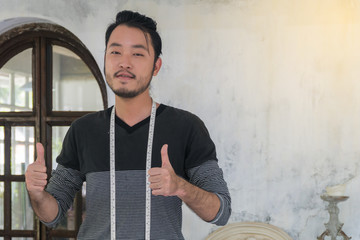 Fashion designer Asian young man standing thumbs up in the studio.