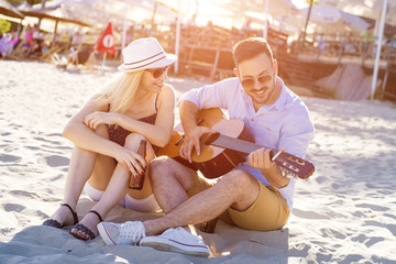 Beautiful loving couple playing guitar on the beach