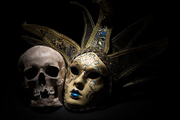 Human skull with venetian mask on a black background. Theater and drama concept
