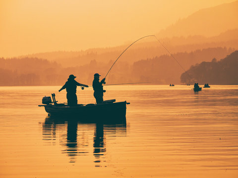 Silhouette of man fishing on lake from boat at sunset. Lake of Menteith, Stirlingshire, Scotland, UK