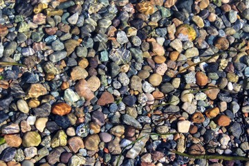Stones on sea floor under the wave