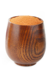 ground red chili pepperr in wooden cup isolated