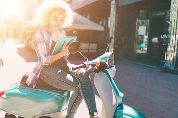 Cheerful young woman is sitting on scooter and using digital tablet