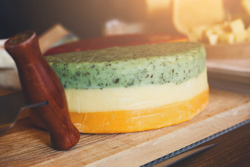 Cheese background. Colored gouda with herbs on wooden plate