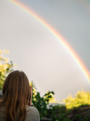 girl photographs a rainbow