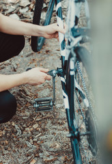 man repair of a bicycle in the forest