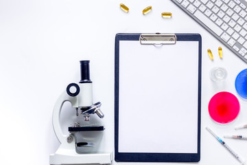 Medical tests. Work table of doctor witn microscope, Petri dish, syringe on white background top view copyspace mockup
